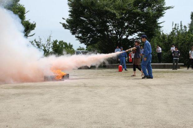 少し火に近づき消火器を噴射する女子学生