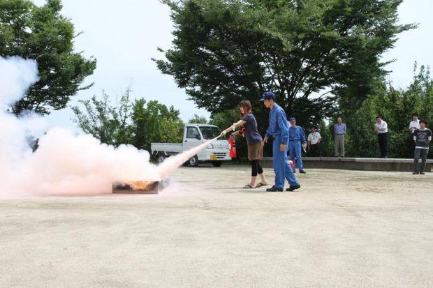 火に近づき消火器を噴射する女子学生