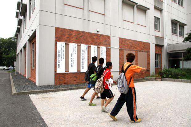 看板の前を歩く学生さん