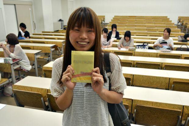 手紙を持つ笑顔の女子学生