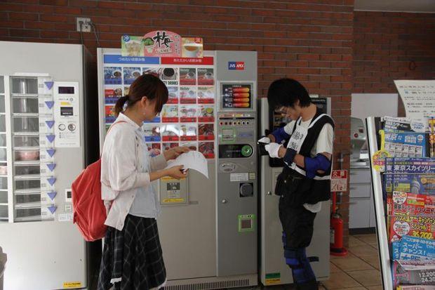 高齢者体験スーツで自動販売機のジュースを買う体験