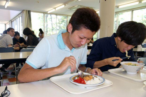 カツカレーを食べる男子学生