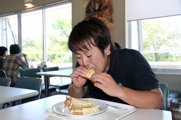 ミックスホットサンドイッチを食べる男子学生