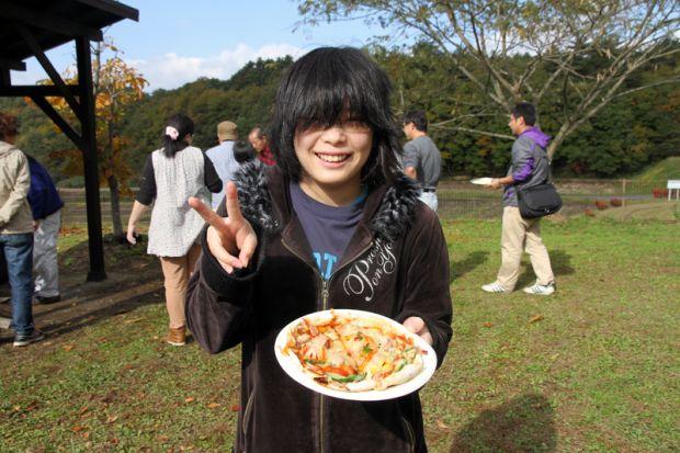 ピザを持ってピースする学生