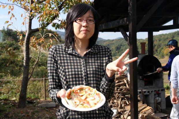 焼きあがったピザを持つ女学生