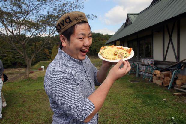 ピザを食べるポーズをする学生