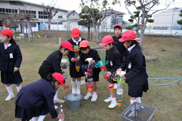自分のペットボトルロケットの発射準備をする小学生