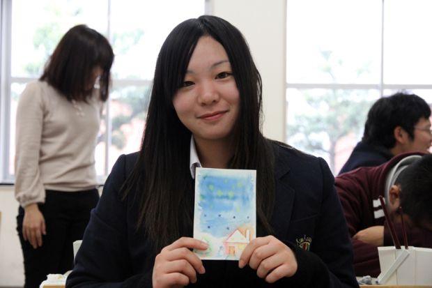 制作したクリスマスカードを持つ女子高生
