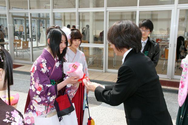 中川先生から花を受け取る卒業生