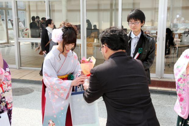 田丸先生から花を受け取る卒業生
