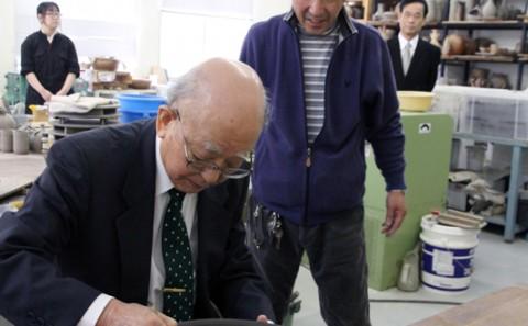 芸術学部岡田教授の作品に鈴木特別栄誉教授が座右の名を記す。