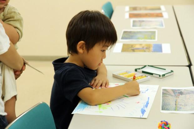 クレヨンで絵を描く小学生