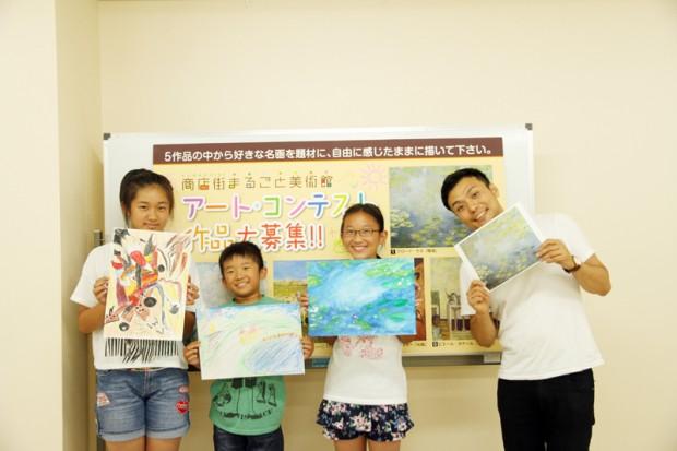 川上先生と完成した作品を持つ小学生