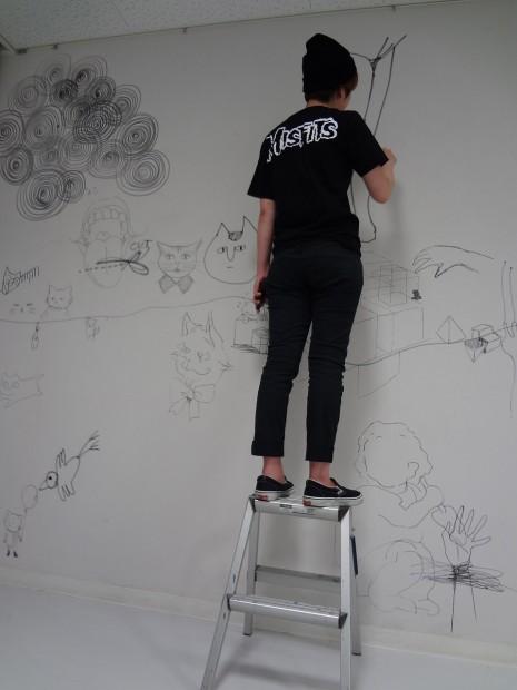 脚立に乗って壁に直接ドローイング中