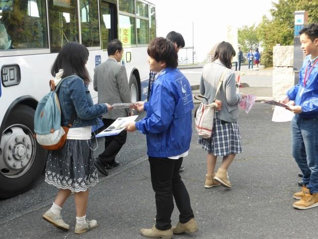 バスから降りてくる学生に啓発チラシを手渡す