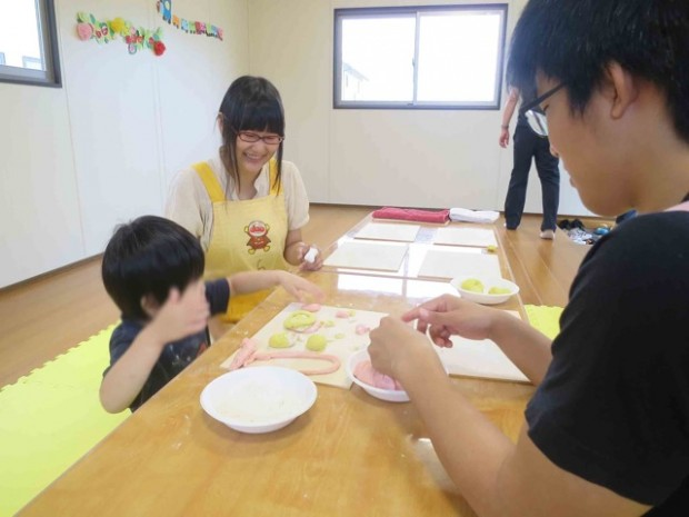 学生とねんど遊びをする子ども