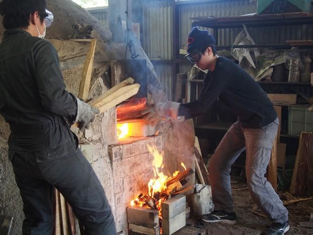 登り窯に松の割木を焚べる学生さん