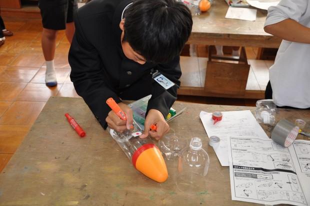 ペットボトルロケットに模様を書く小学生