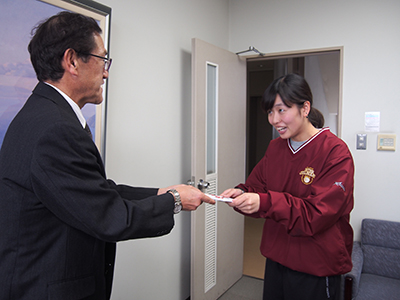 女子バスケ部学生代表に援助金を贈与する様子