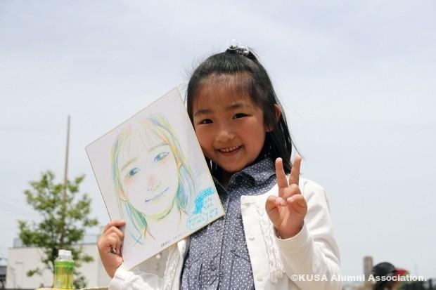 似顔絵を描いてもらった女の子(ピース)