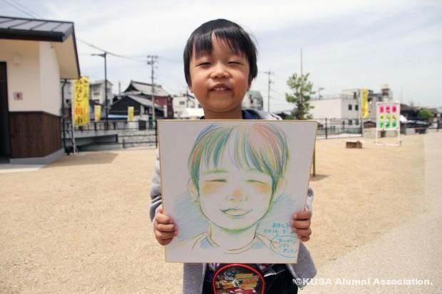似顔絵を描いてもらった男の子