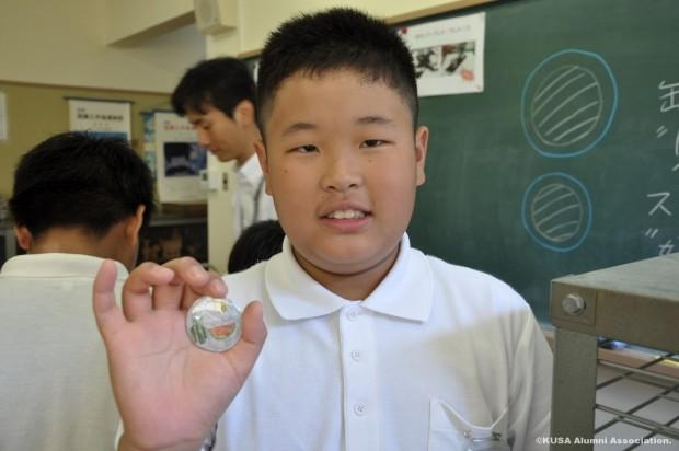 完成した缶バッチを持つ小学生