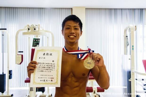 表彰状とメダルを持つ安田さん
