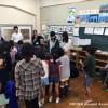 ドクターフィッシュの水槽に集まる小学生