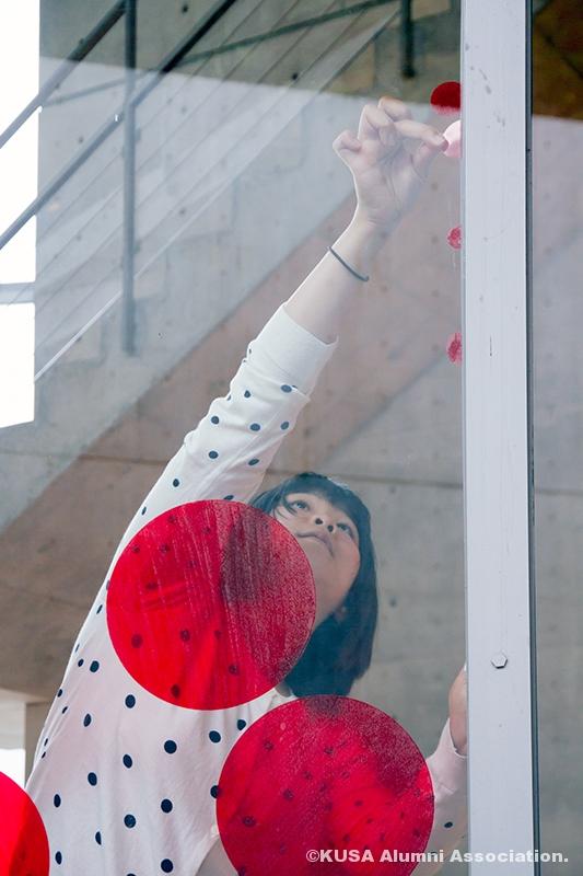 水玉のシールを貼る女子学生