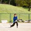 低めのボールを打つ女子学生
