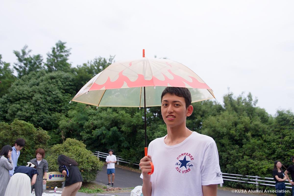 制作した傘を持つ男子学生