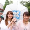 制作した傘を持つ笑顔の女子学生