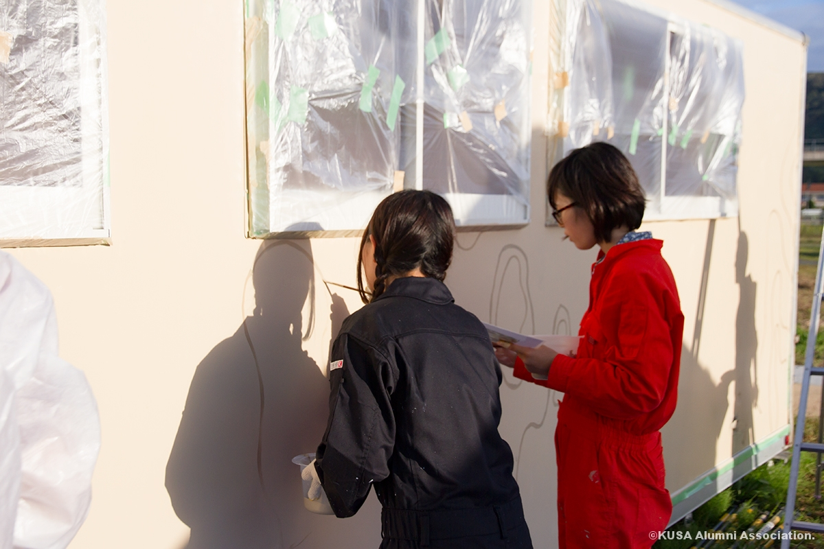コンテナに絵を描く女子学生