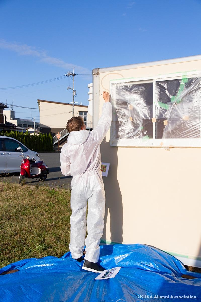 コンテナに絵を描く留学生