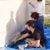 コンテナに絵を描く男子学生